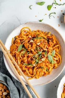 hot chili chicken noodles in a bowl with chopsticks
