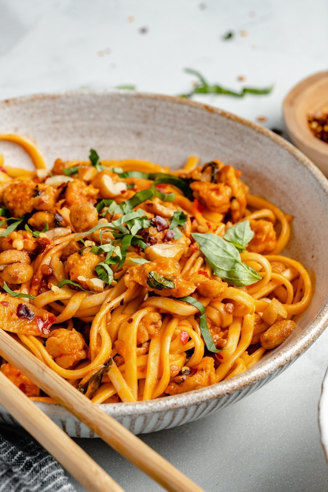 sweet and spicy chicken noodles in a bowl topped with peanuts and basil