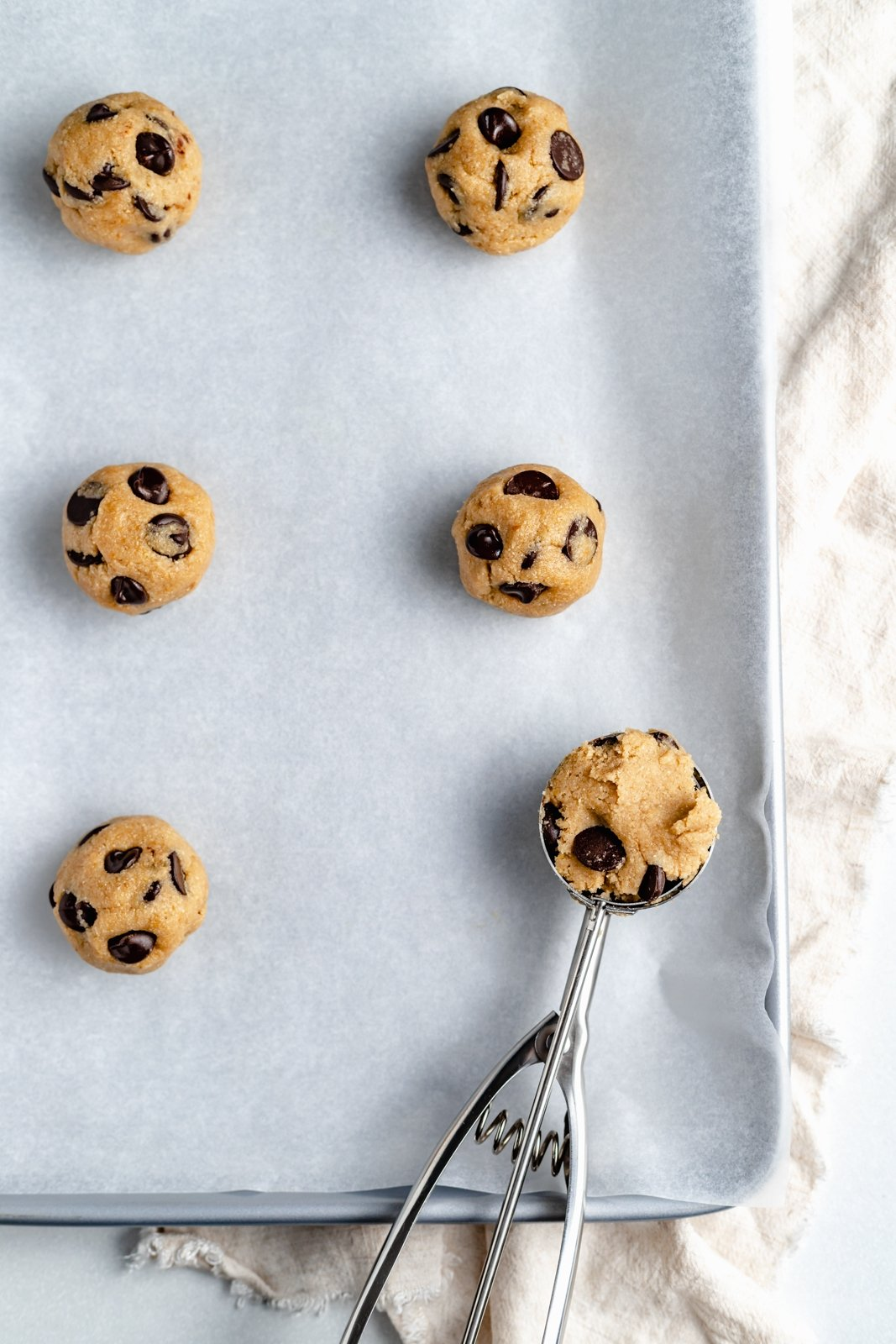 unbaked vegan and gluten free chocolate chip cookie dough balls on a baking sheet
