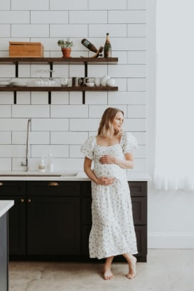woman in a kitchen wearing a long white dress