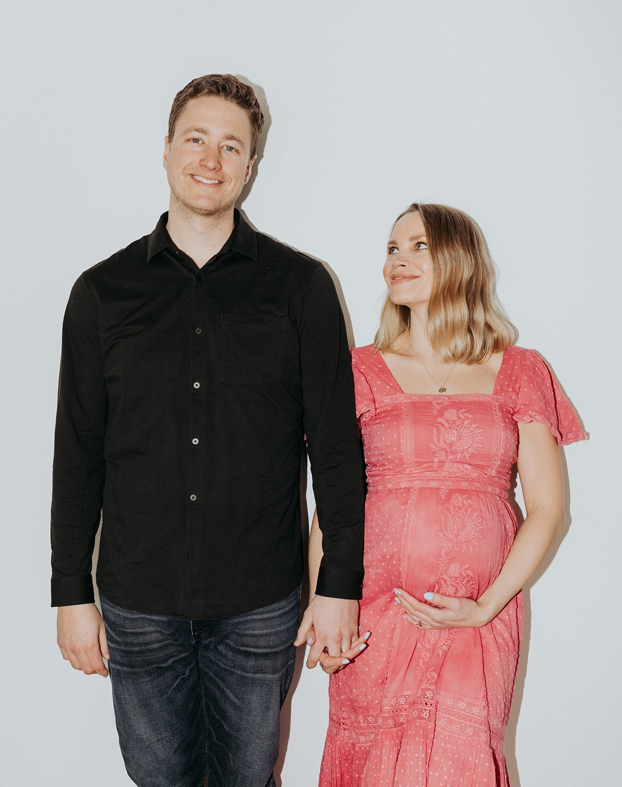 man holding hands with a pregnant woman in a pink dress