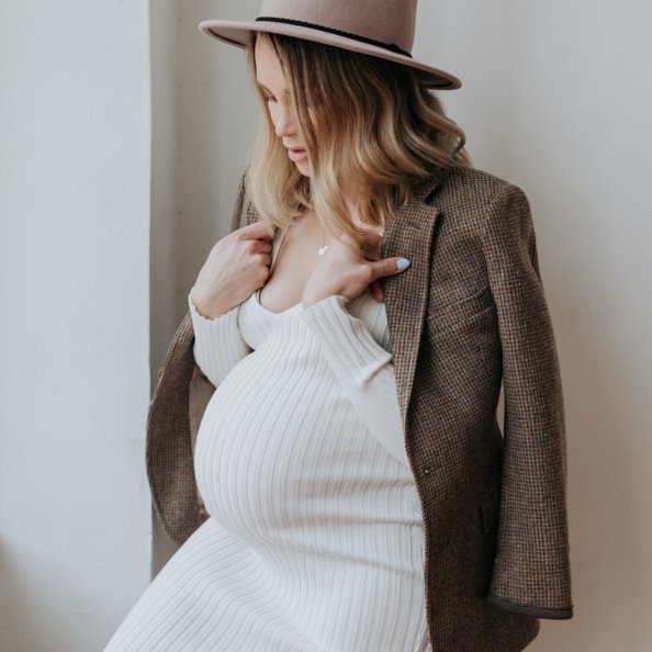 pregnant woman wearing a white dress, jacket and hat