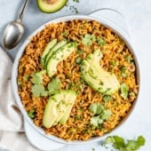arroz con gandules in a bowl topped with sliced avocado