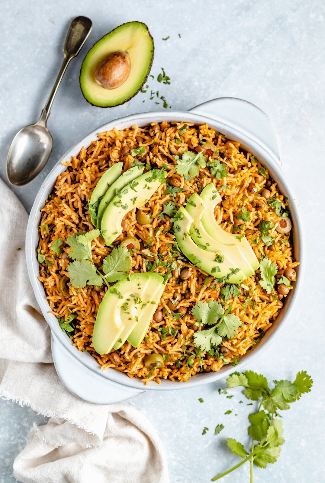 puerto rican arroz con gandules in a bowl topped with avocado slices