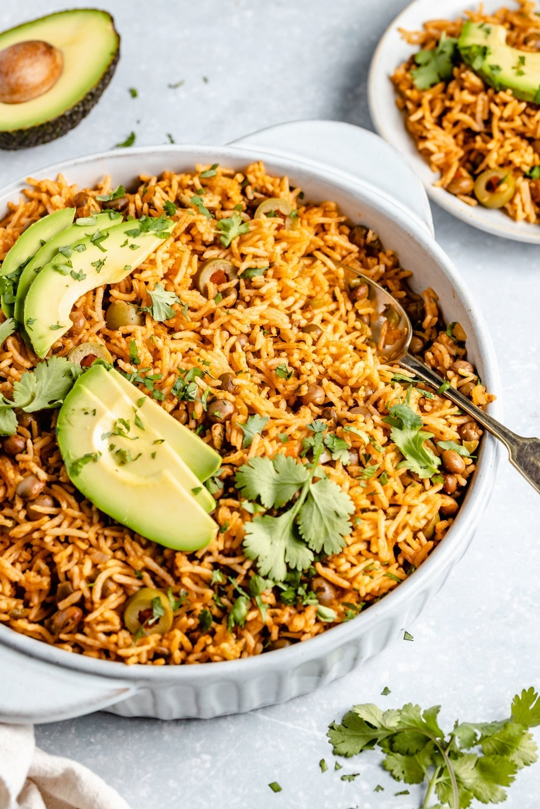 arroz con gandules in a dish topped with cilantro and avocado