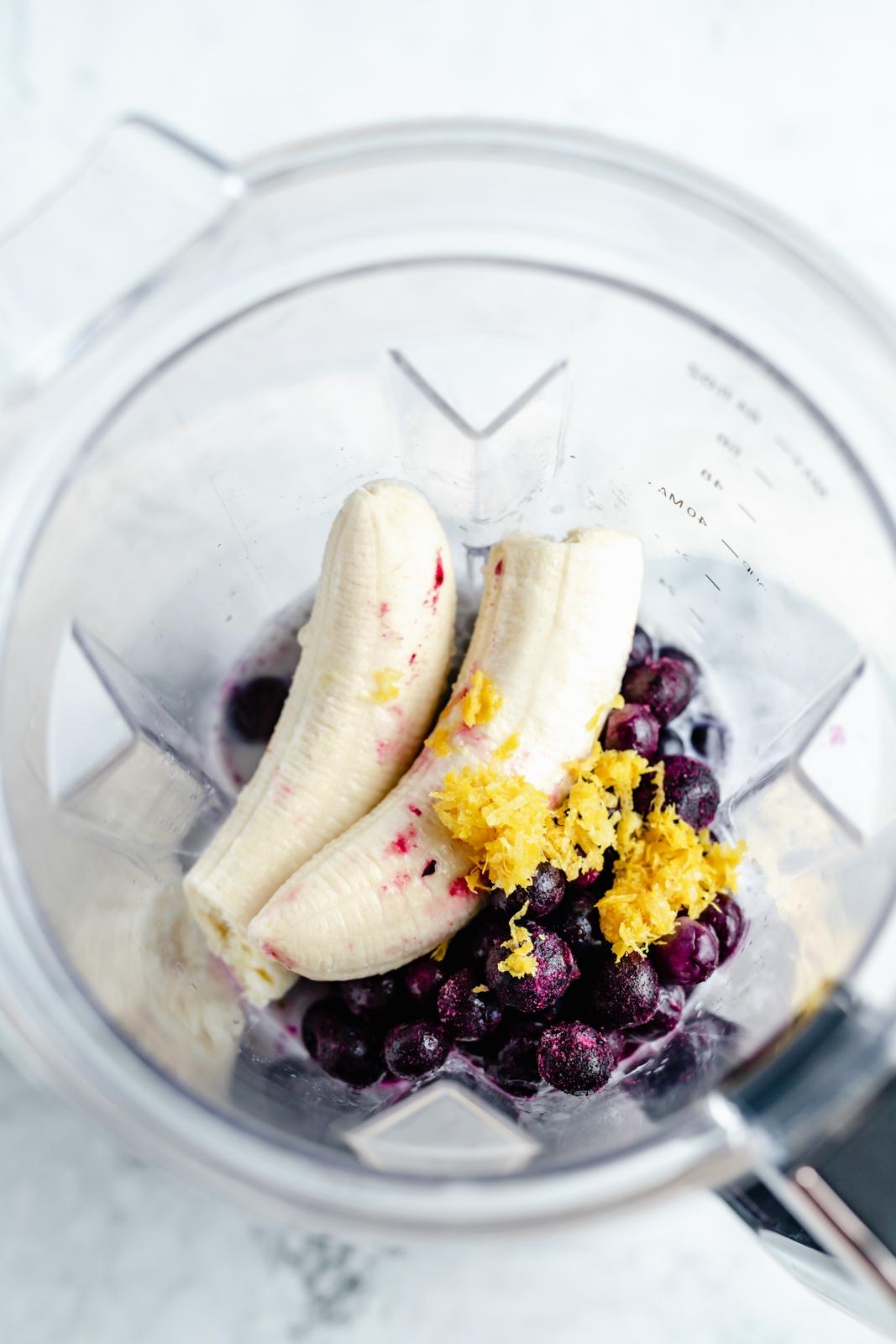 ingredients for a vegan lemon blueberry smoothie in a blender