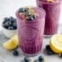 lemon blueberry smoothie in a glass topped with blueberries