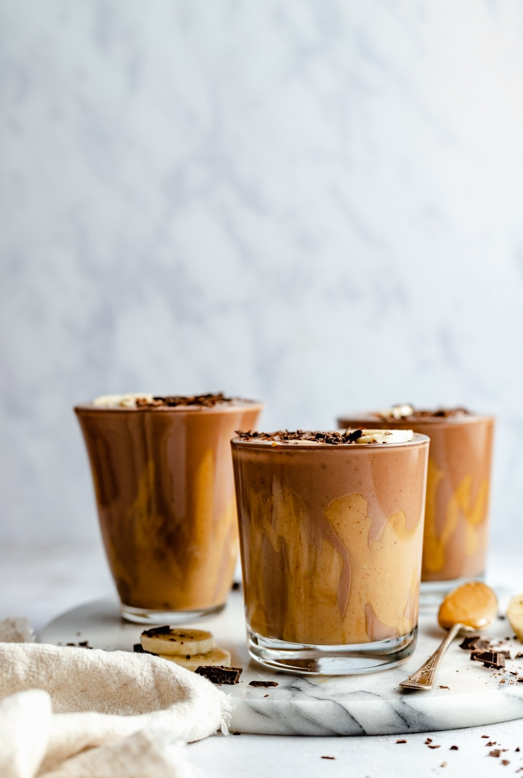 three chocolate peanut butter banana smoothies on a marble board