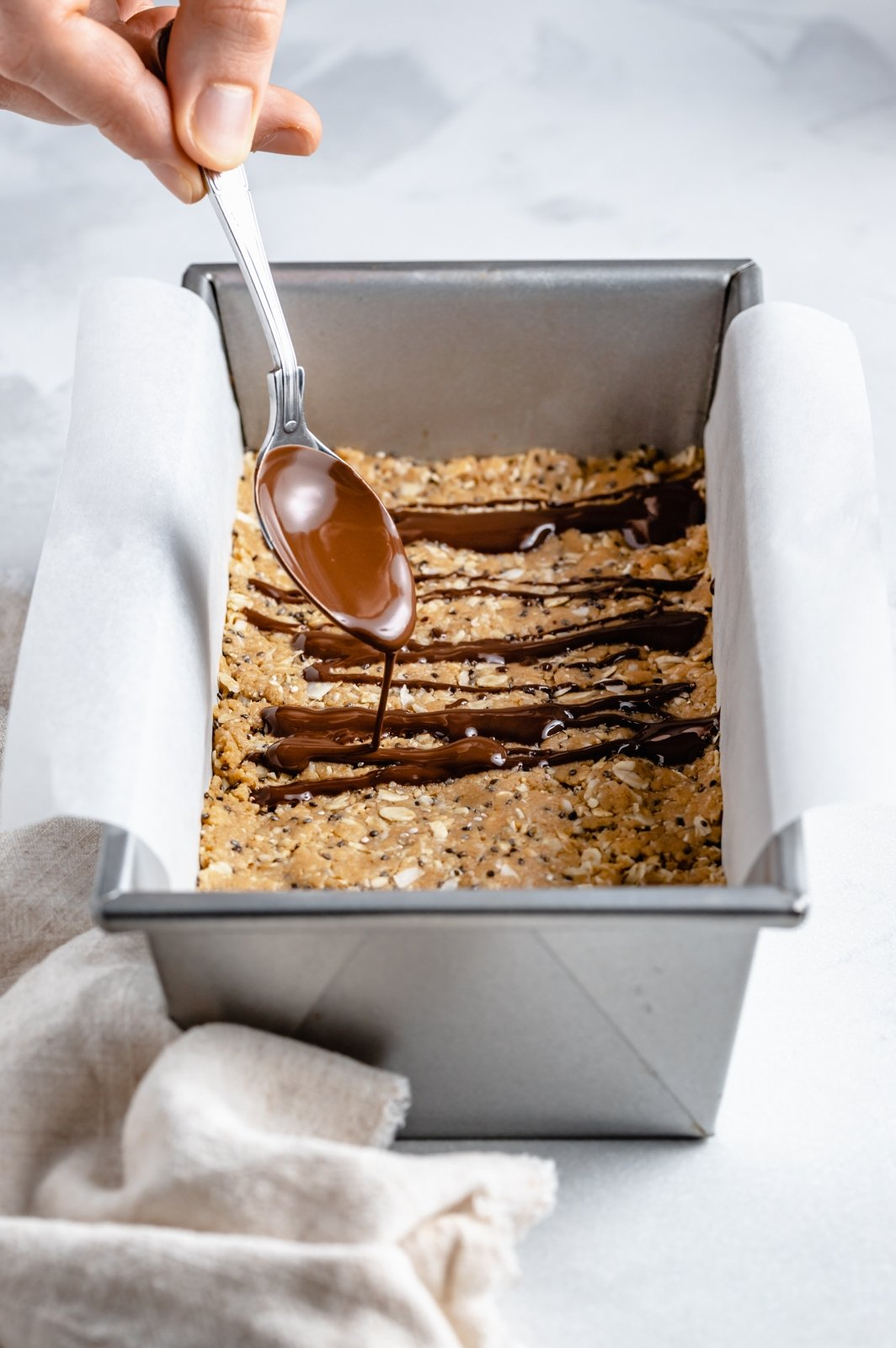 drizzling chocolate onto coconut protein bars
