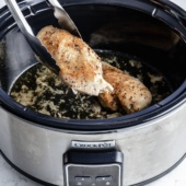 pulling a chicken breast out of a slow cooker