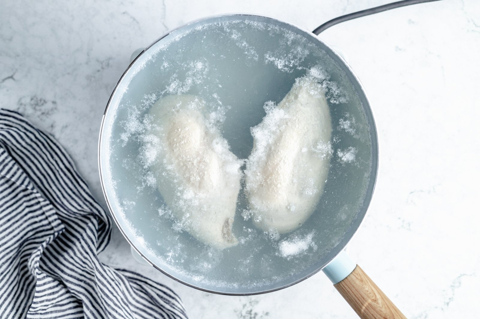 poaching two chicken breasts in a pot