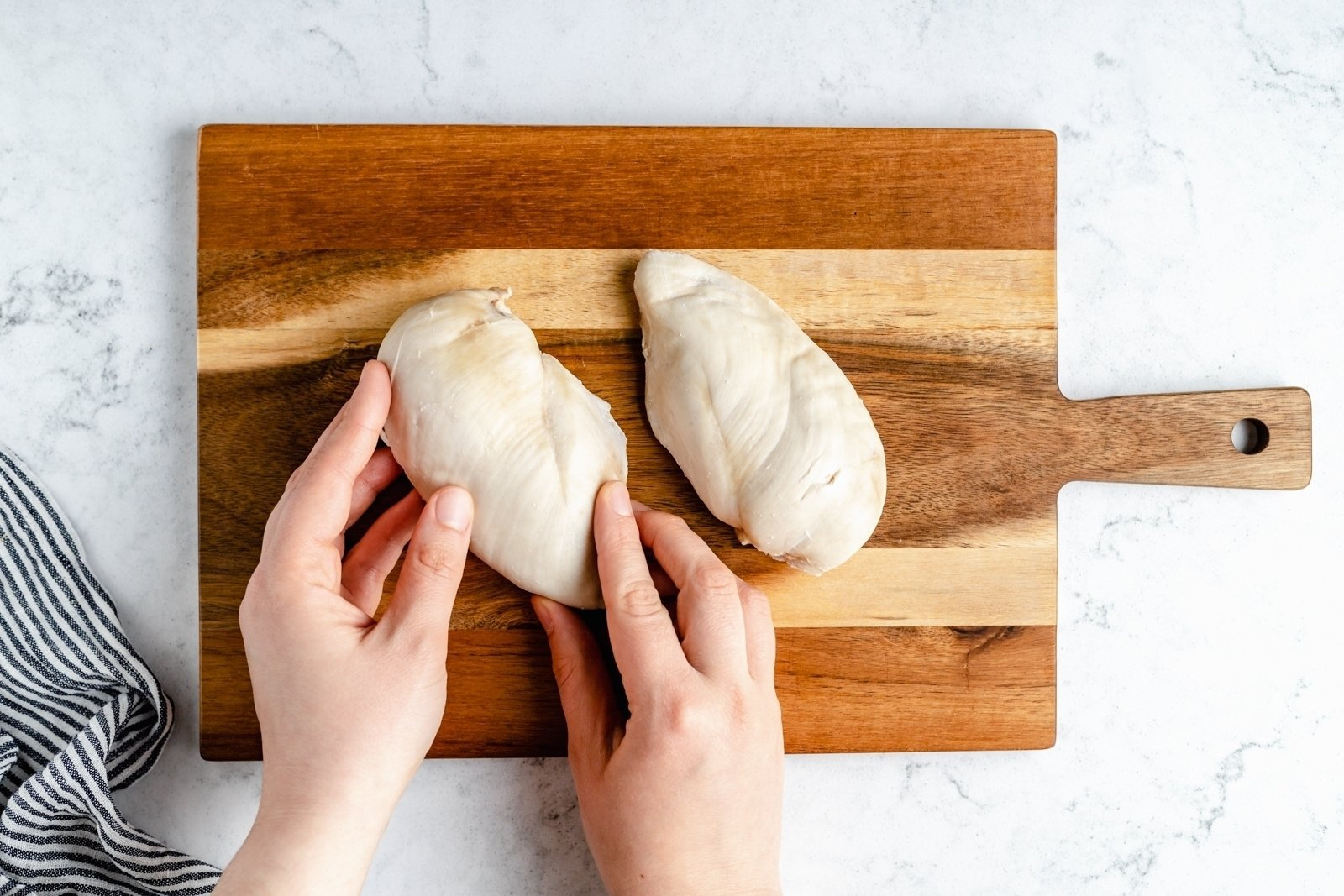 hands holding cooked chicken breast on a cutting board