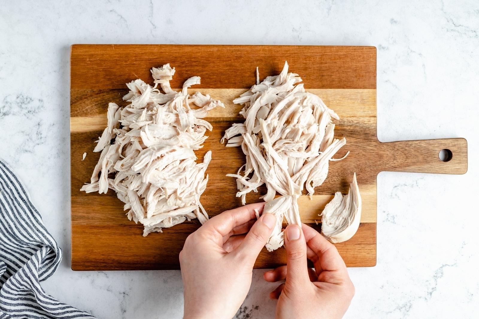 hands shredding a chicken breast on a cutting board
