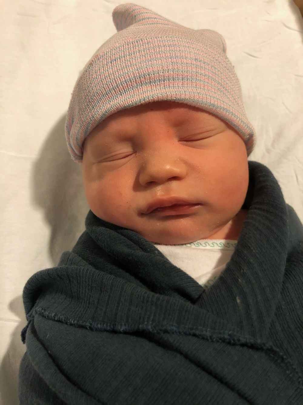 baby viggo with a hat on wrapped in a swaddle