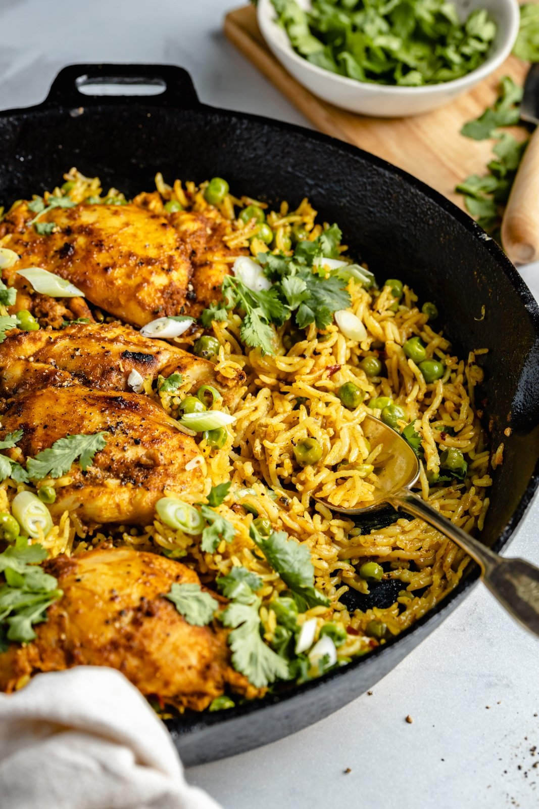 healthy tandoori chicken in a skillet with rice and a spoon