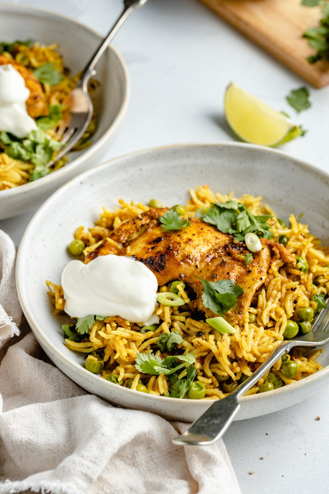 tandoori chicken with rice in a bowl topped with yogurt