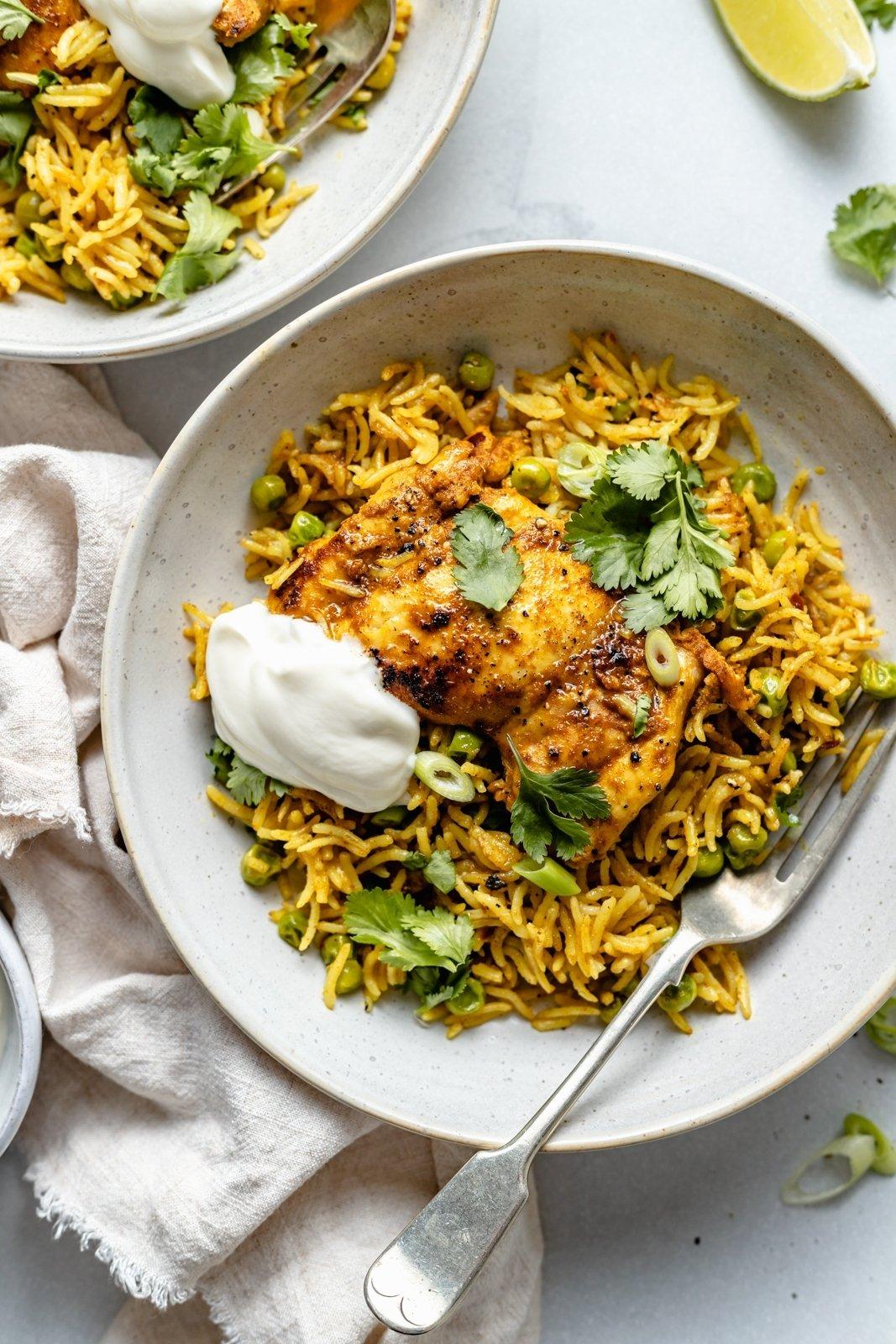 tandoori chicken on a plate with rice and yogurt