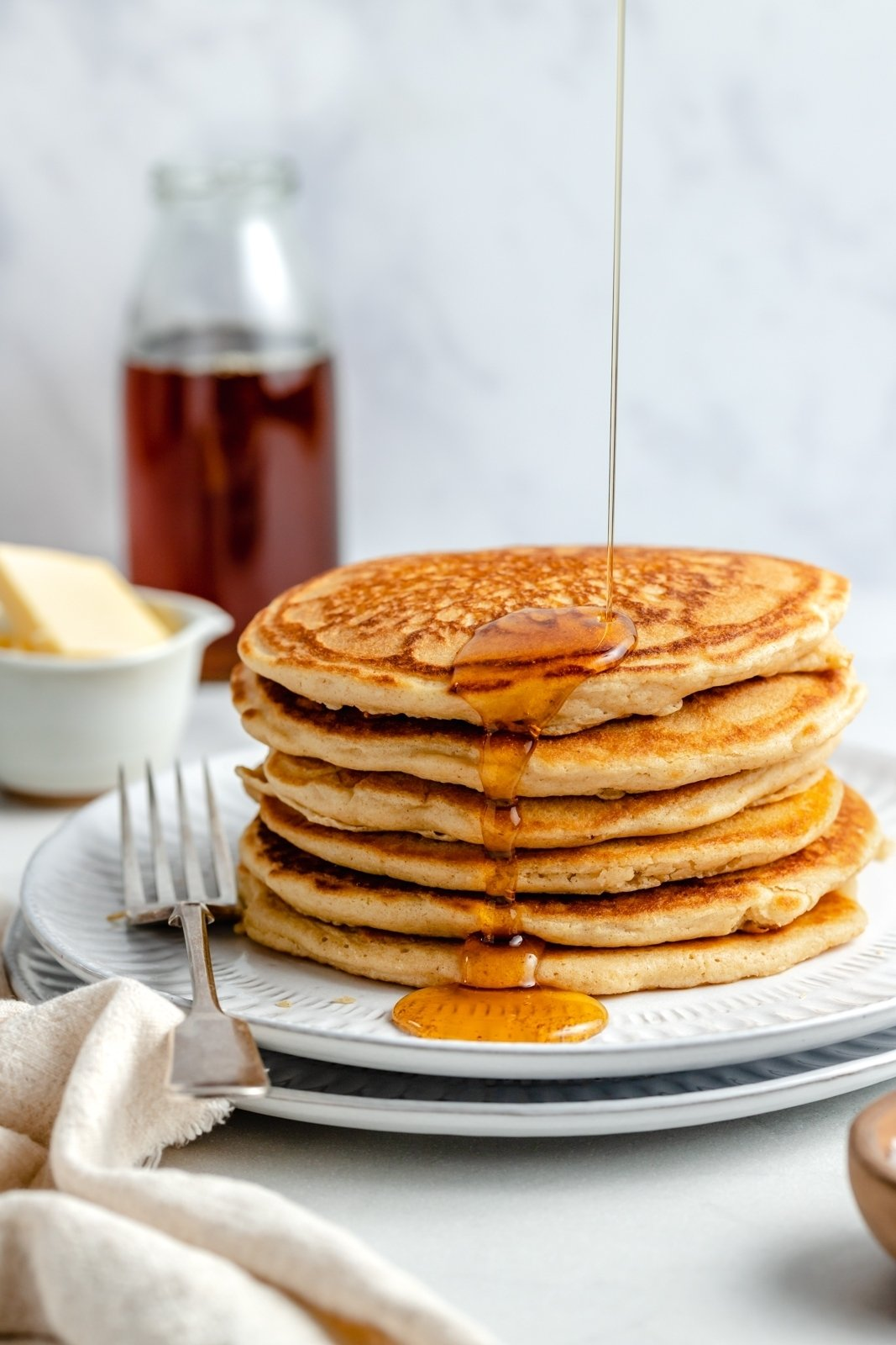 drizzle syrup on a stack of brown butter pancakes