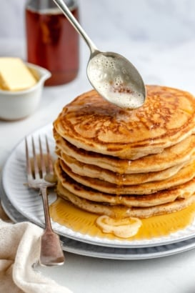 drizzling brown butter onto a stack of brown butter pancakes