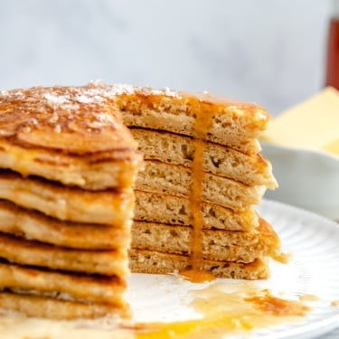 brown butter pancakes in a stack with a slice cut out