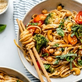 vegan stir fry noodles in a bowl with chopsticks
