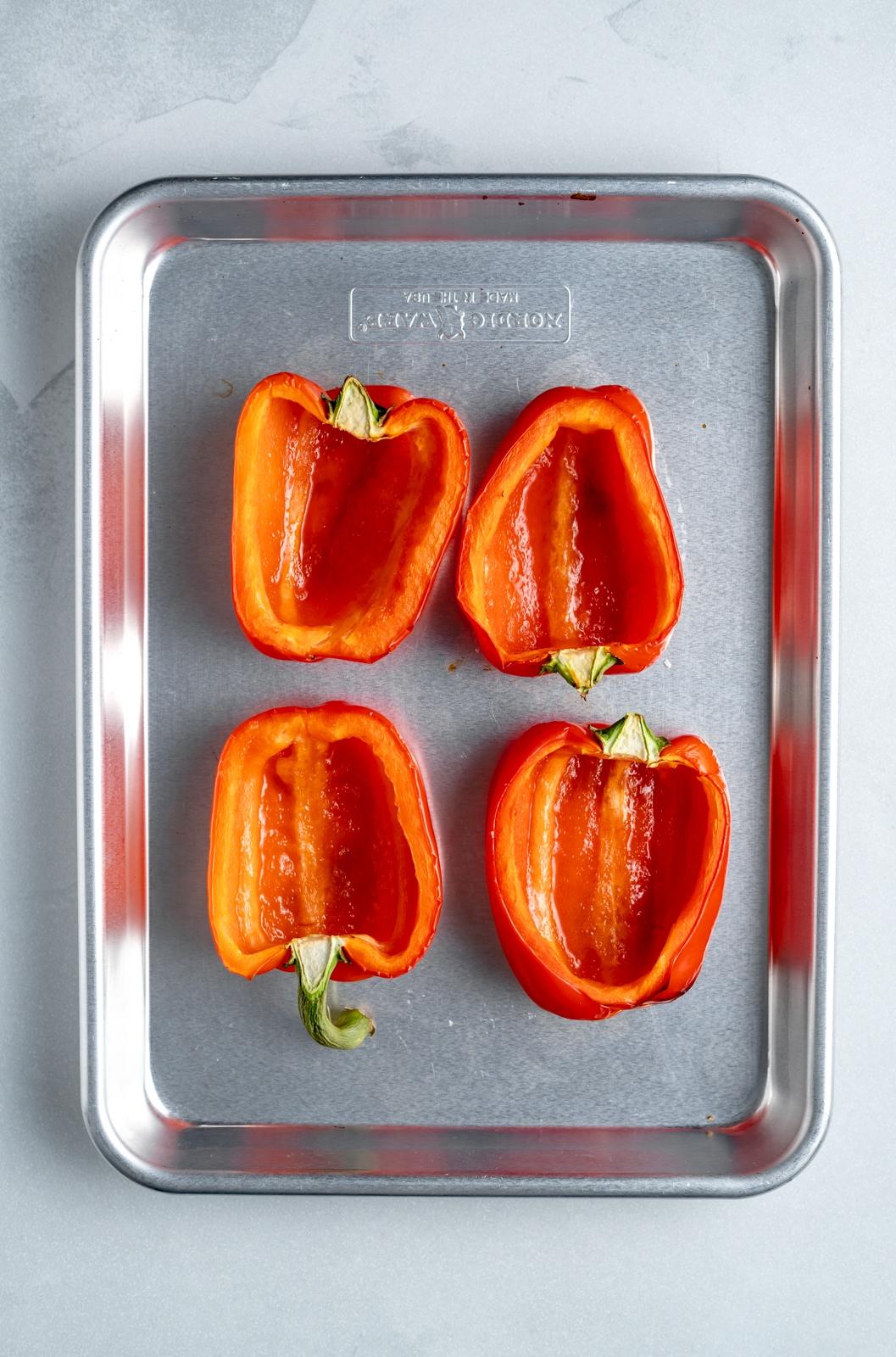 four red bell pepper halves on a baking sheet