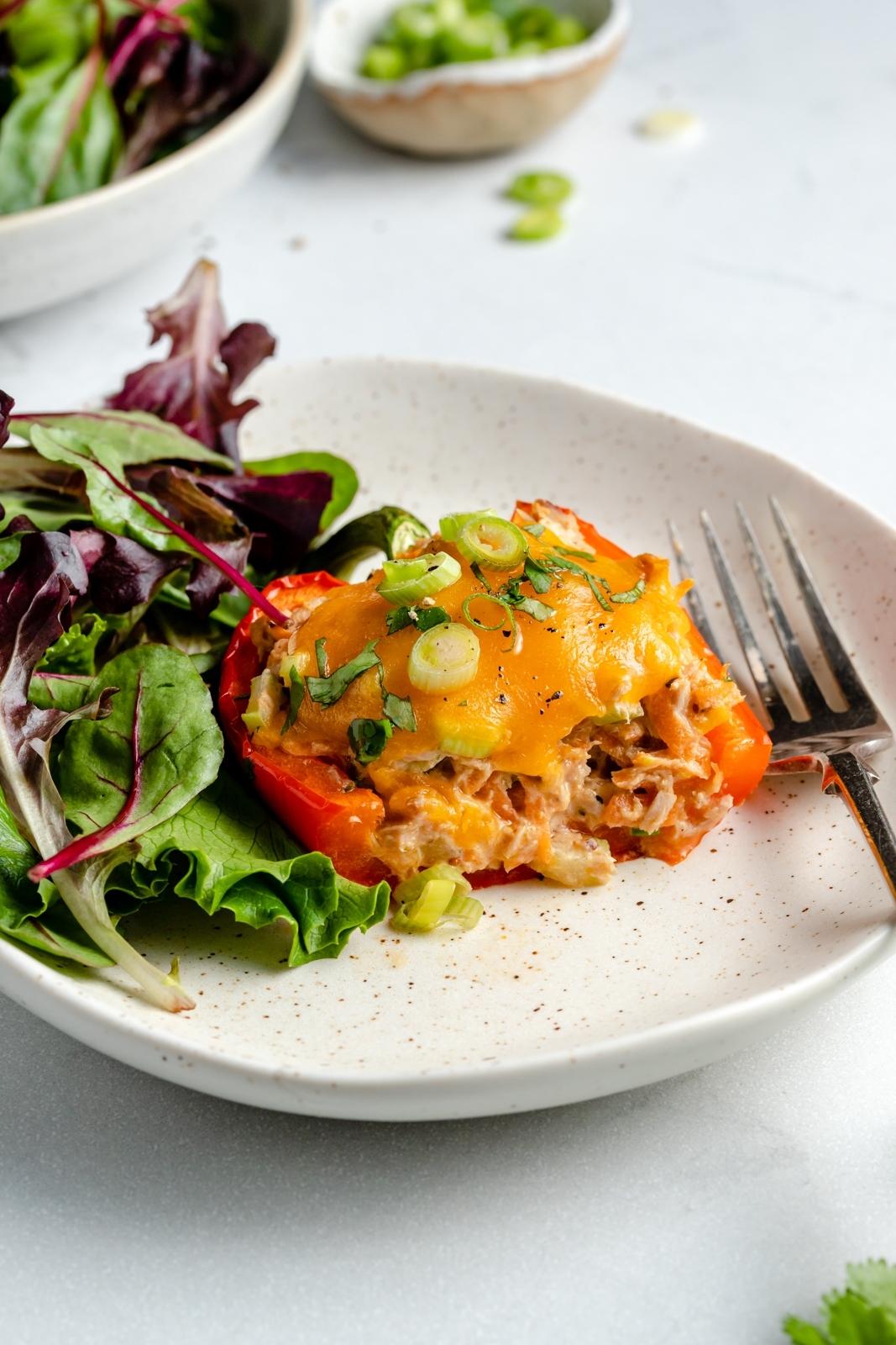 tuna melt stuffed pepper on a plate with a side salad