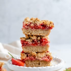 strawberry crumble bars in a stack on a plate