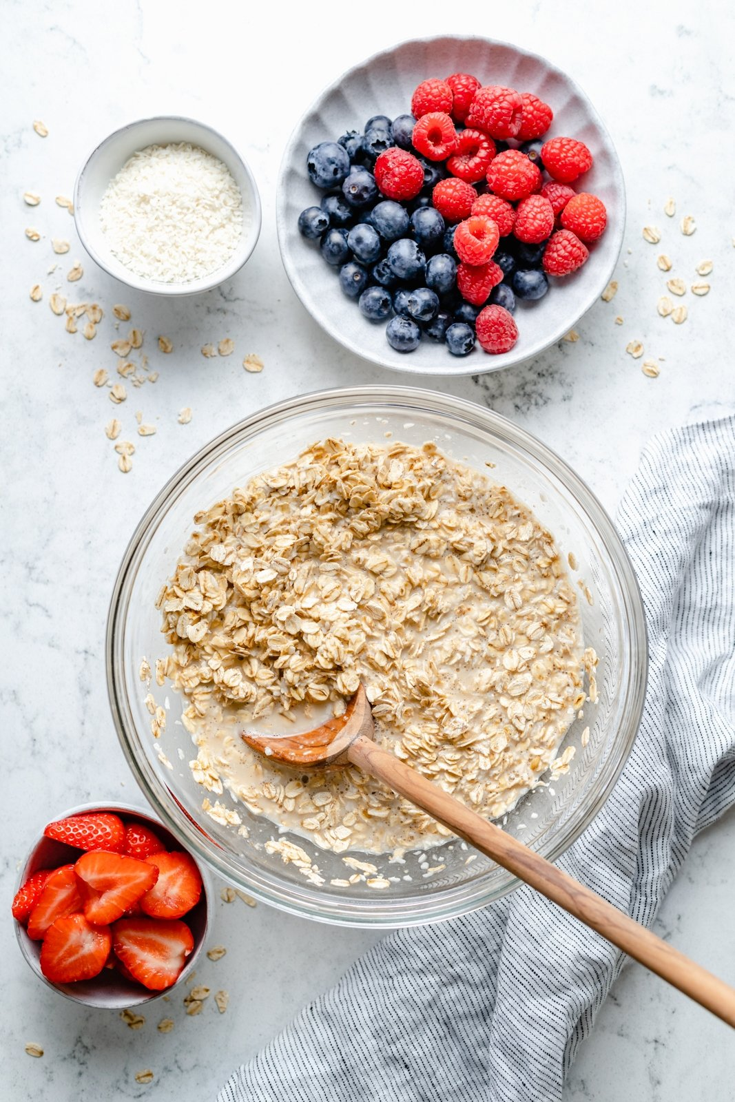 mixing oatmeal next to bowls of berries for berry baked oatmeal