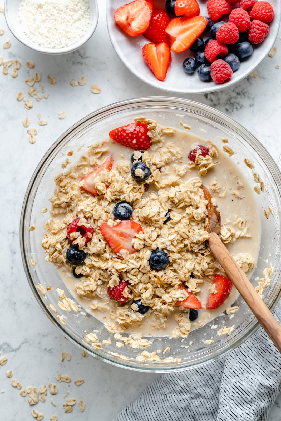 mixing berries and cream baked oatmeal batter in a bowl