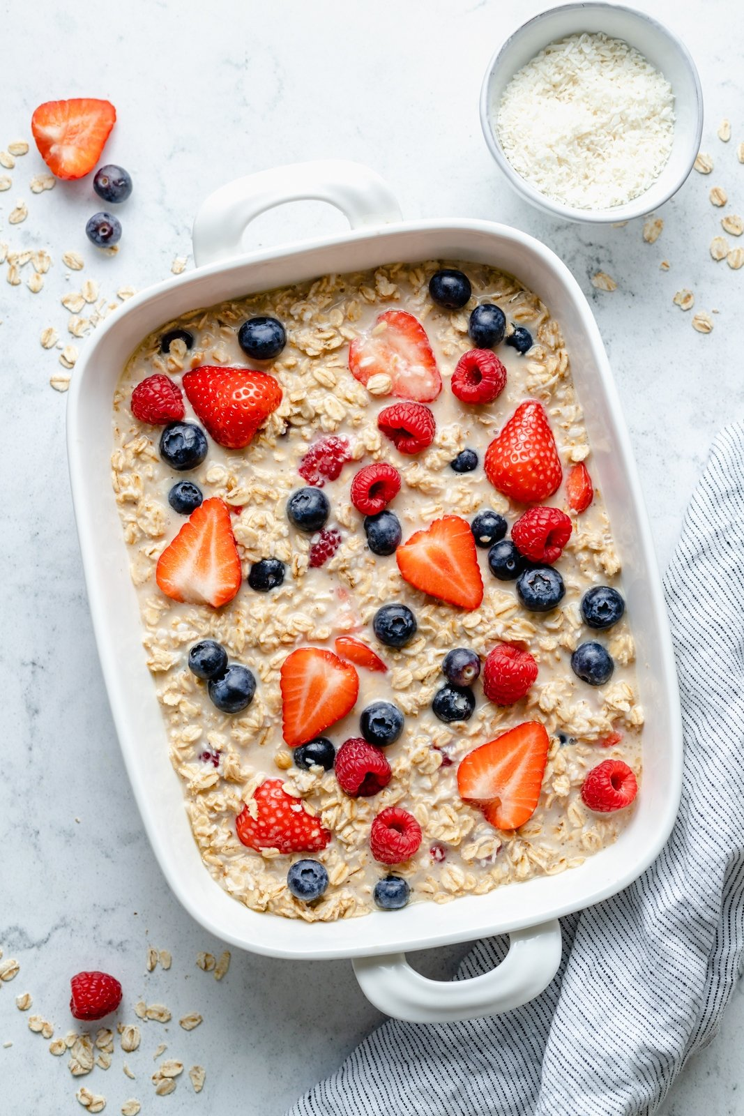 unbaked berries and cream baked oatmeal in a baking dish