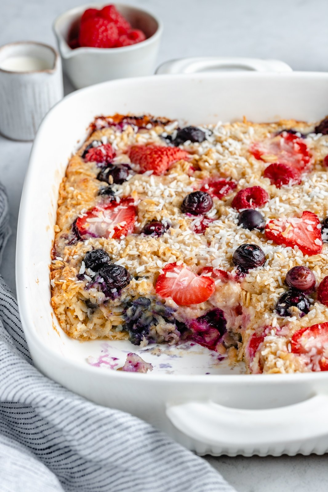 berries and cream baked oatmeal in a baking dish with a slice cut out