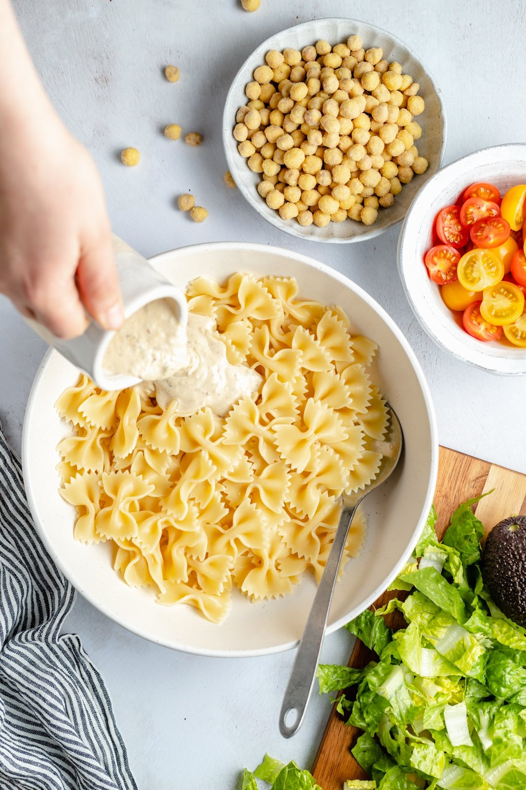 pouring dressing into a bowl of pasta for vegan caesar pasta salad