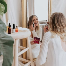 woman putting on makeup in a mirror