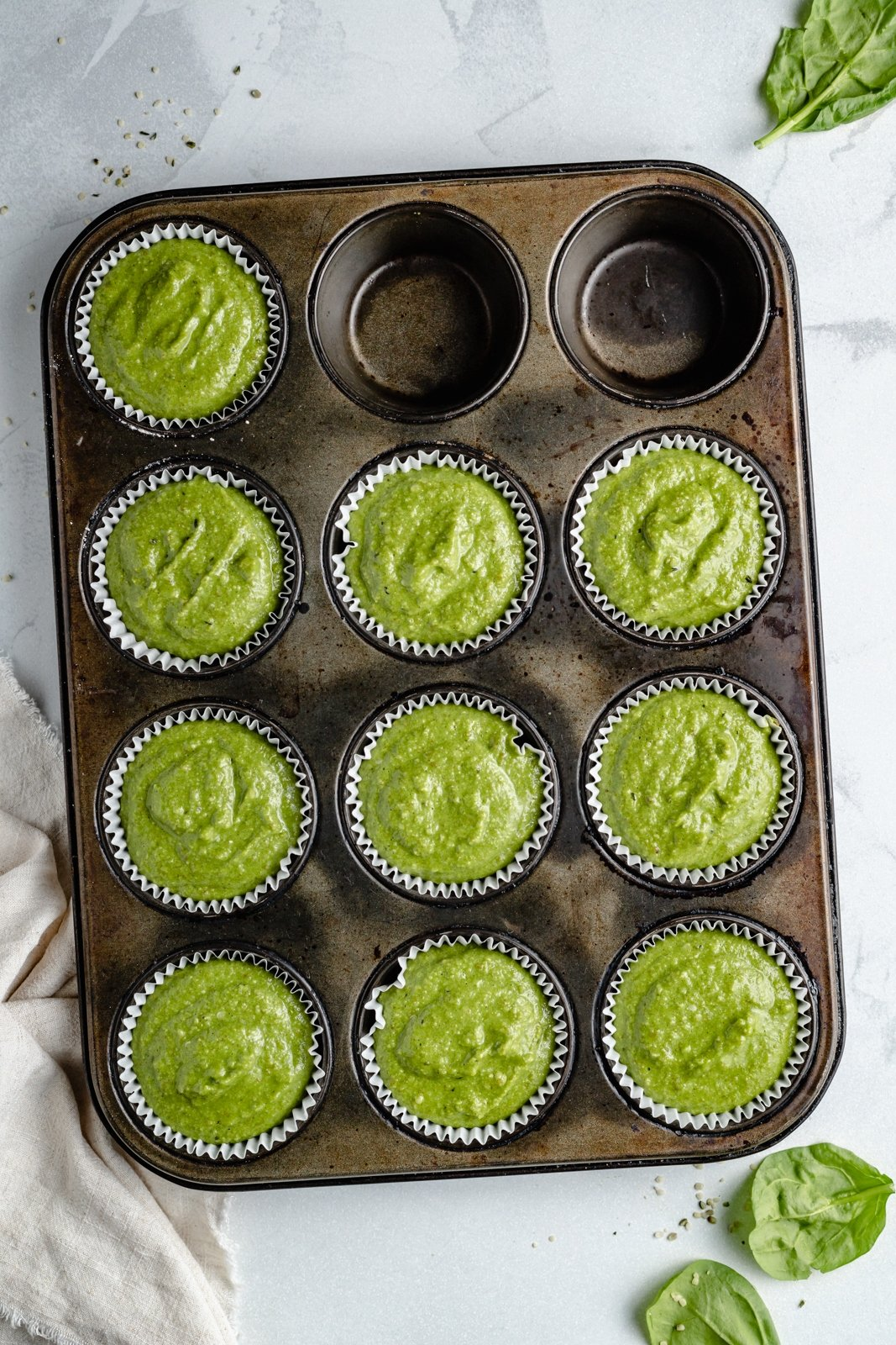 unbaked healthy banana spinach muffins in a muffin tin