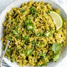green rice in a bowl with a spoon