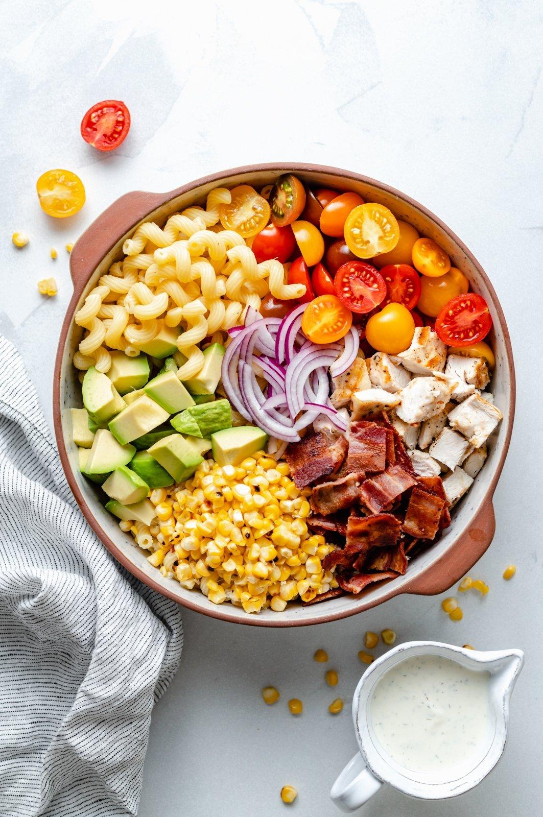 chicken bacon ranch pasta salad unmixed in a bowl