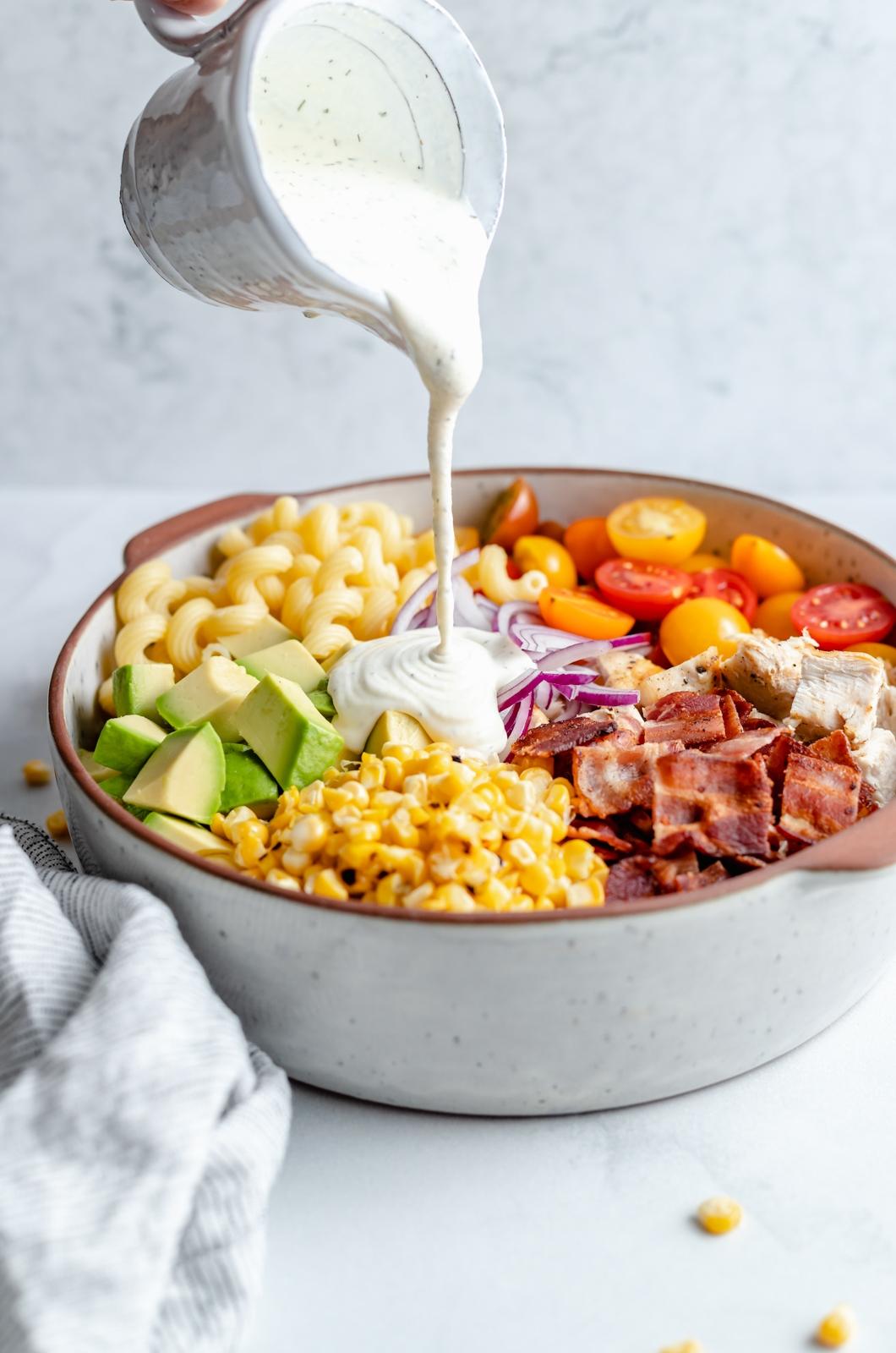 pouring ranch dressing onto a creamy chicken bacon pasta salad