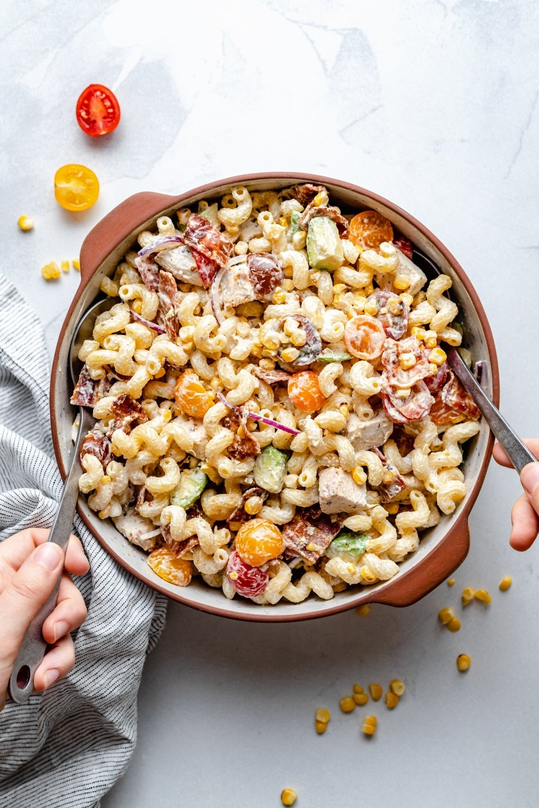 spooning up chicken and bacon pasta salad from a bowl