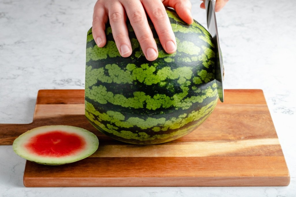 slicing the ends off of a watermelon