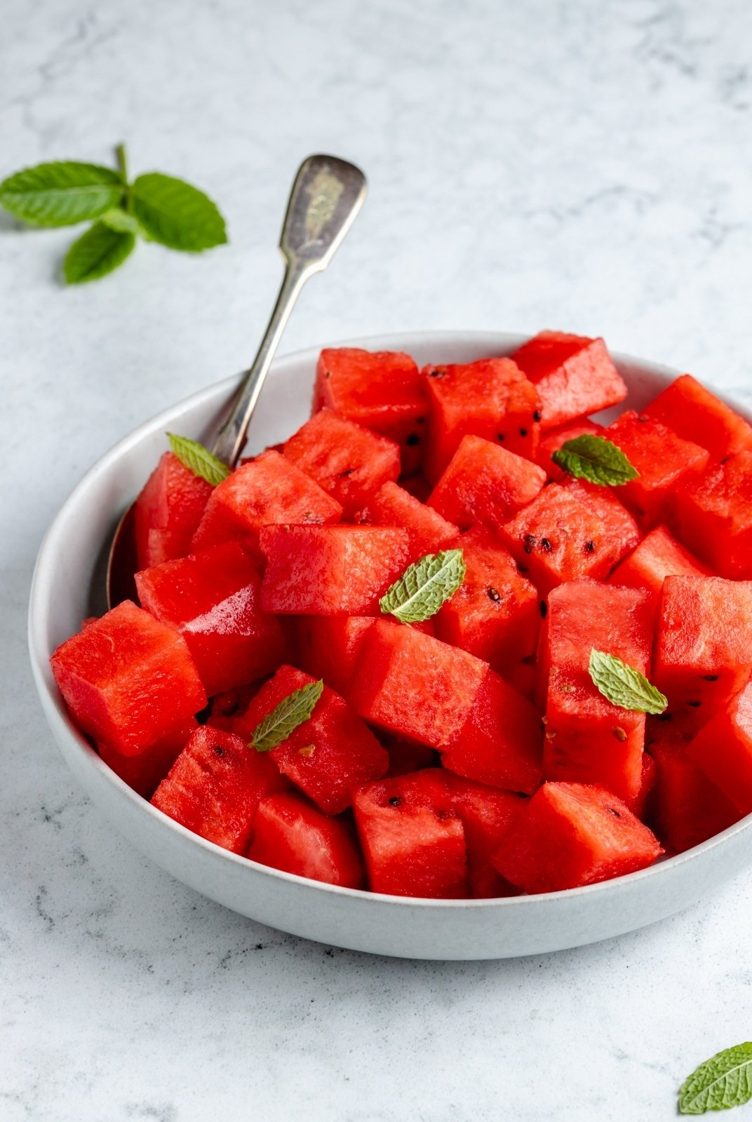 cubed watermelon in a bowl with mint leaves