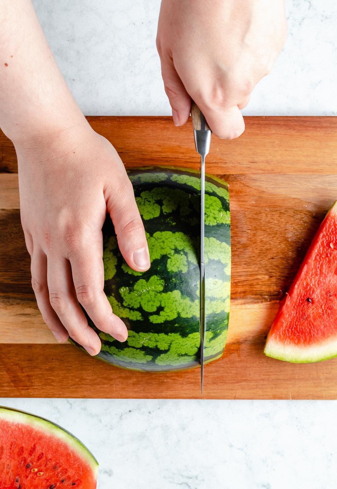 cutting a watermelon half on a cutting board