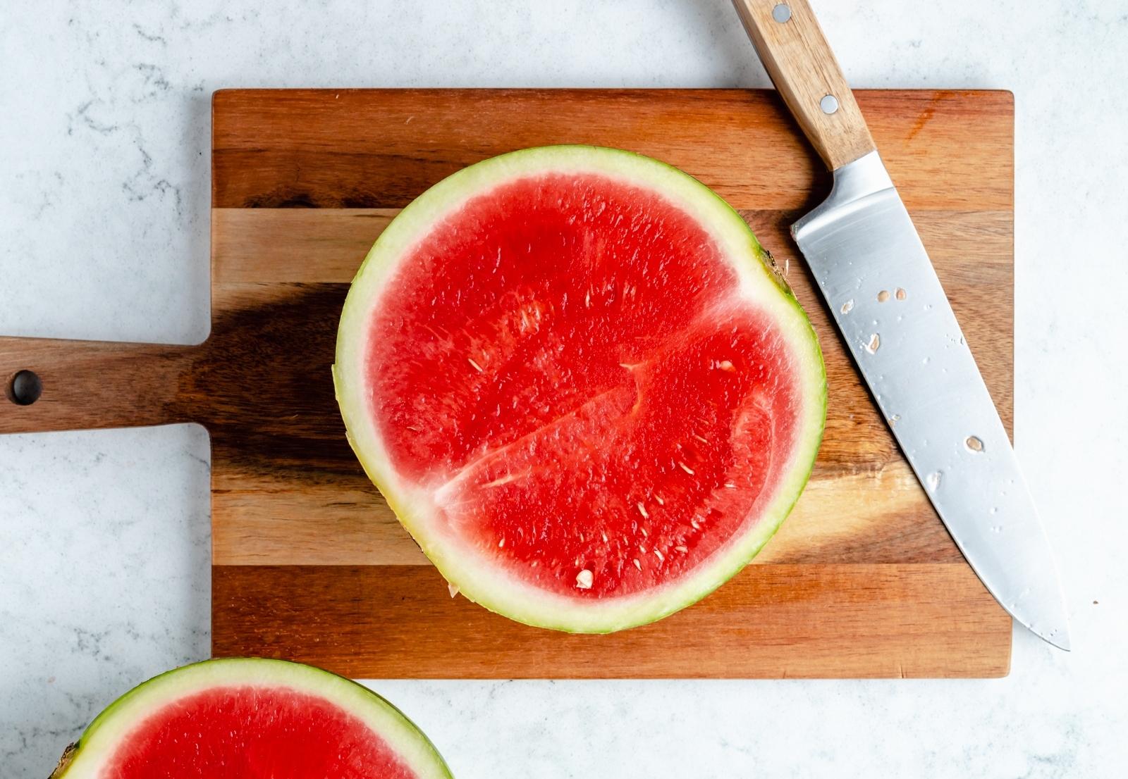 half of a watermelon on a cutting board flesh-side up