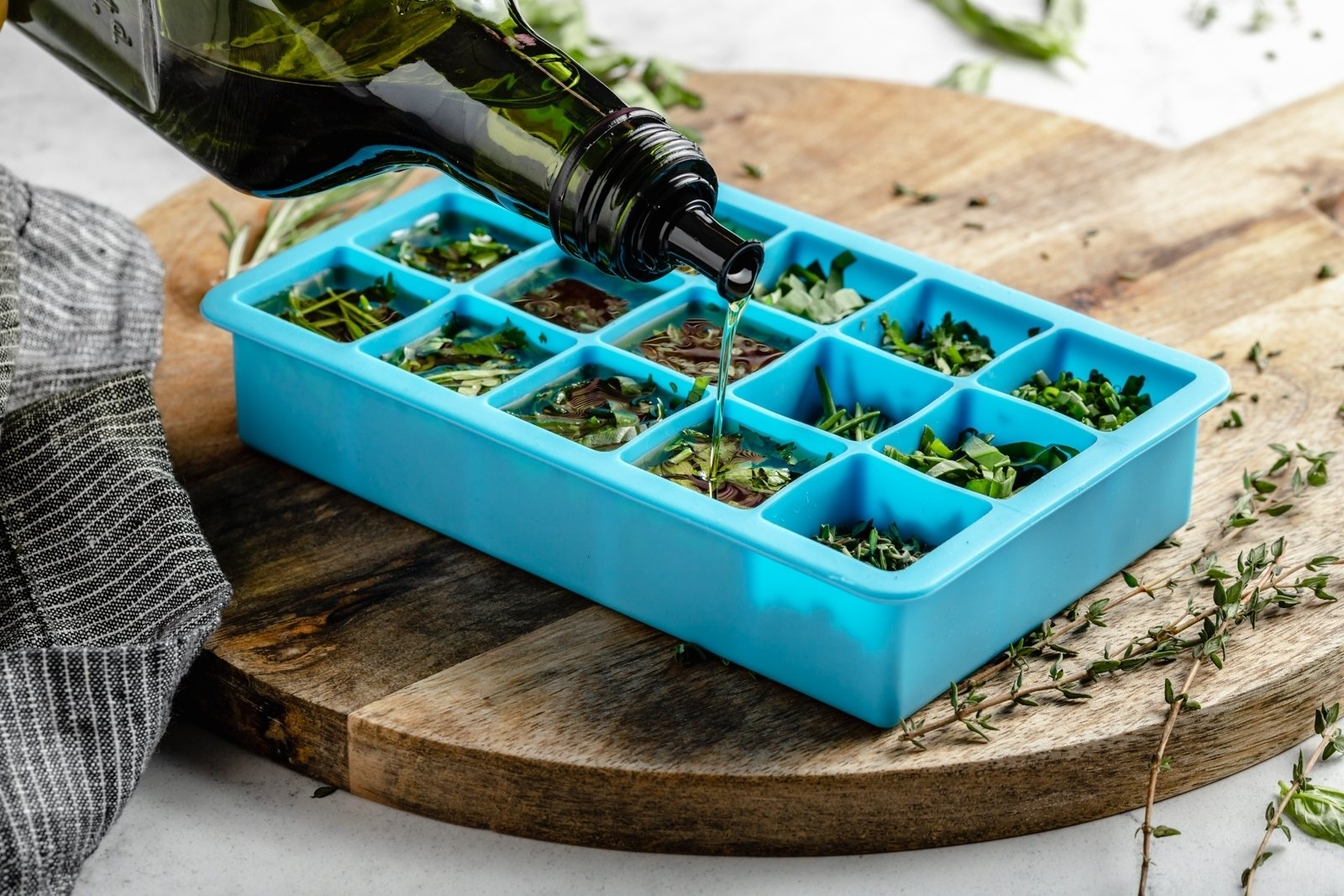 pouring olive oil into an ice tray with fresh herbs