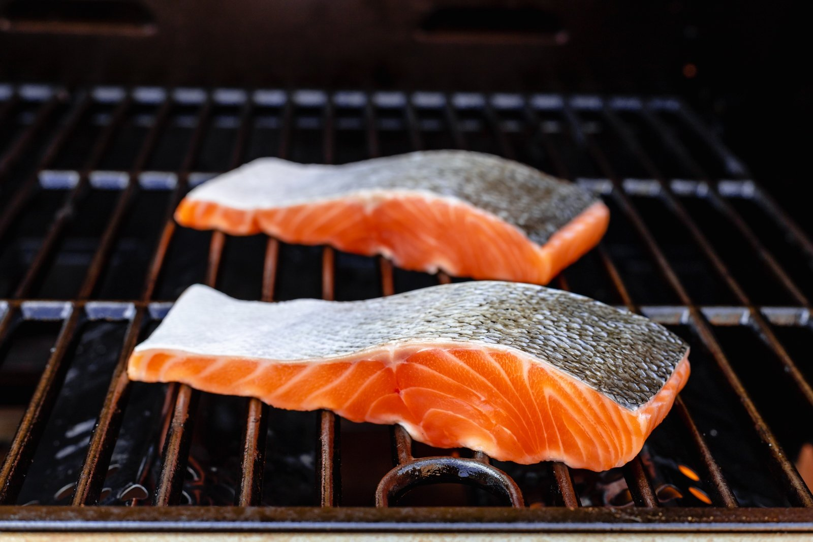 two pieces of salmon on a grill