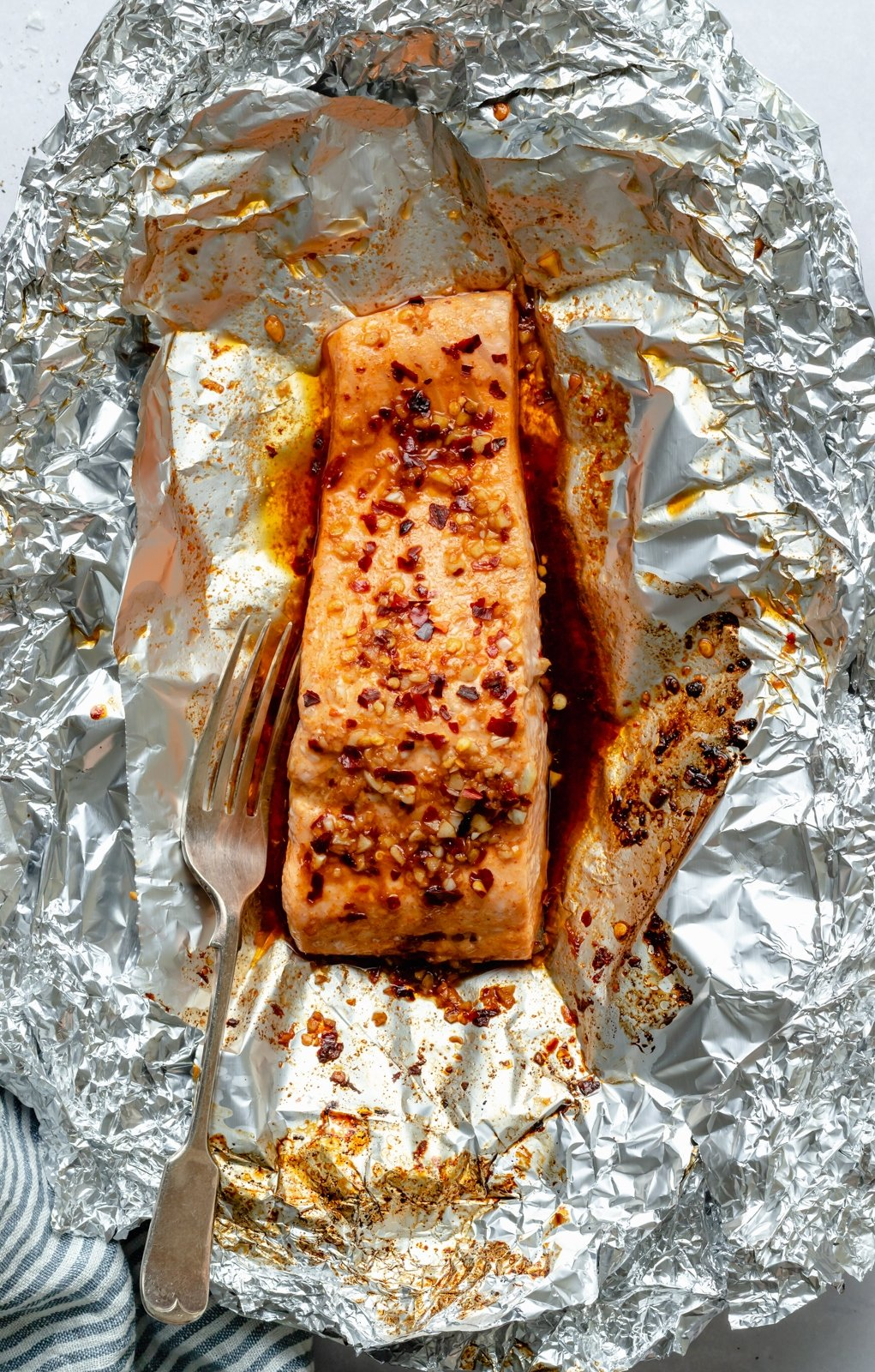 salmon in a foil pack with a fork