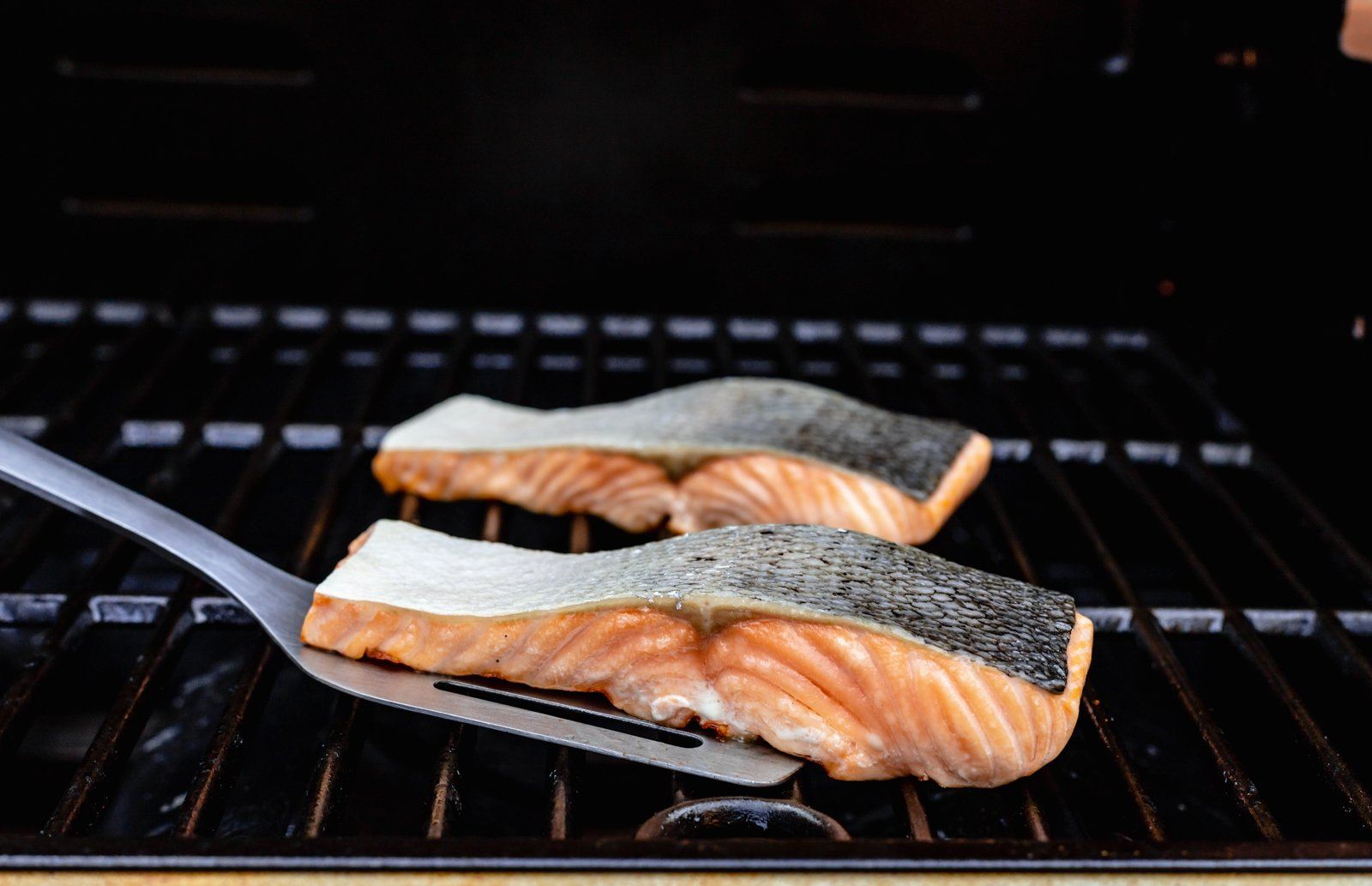 two pieces of salmon on a grill with a spatula