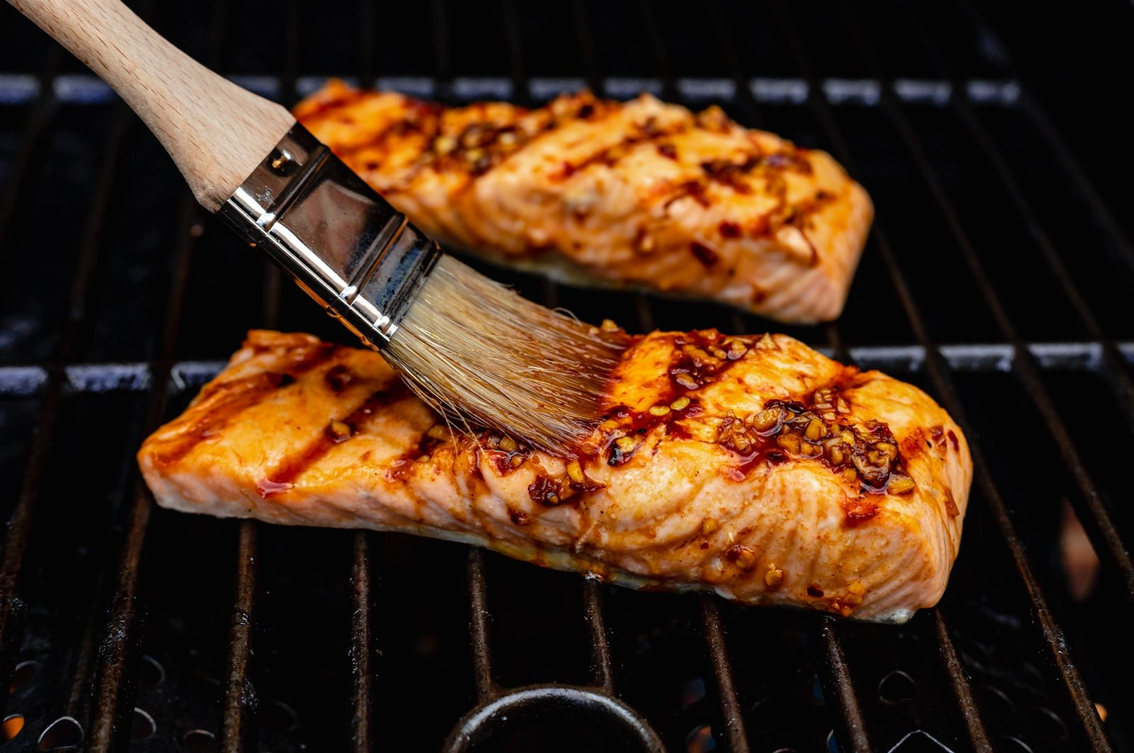 brushing salmon with a marinade on a grill