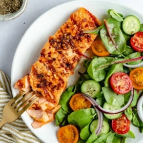 grilled salmon on a plate with a salad