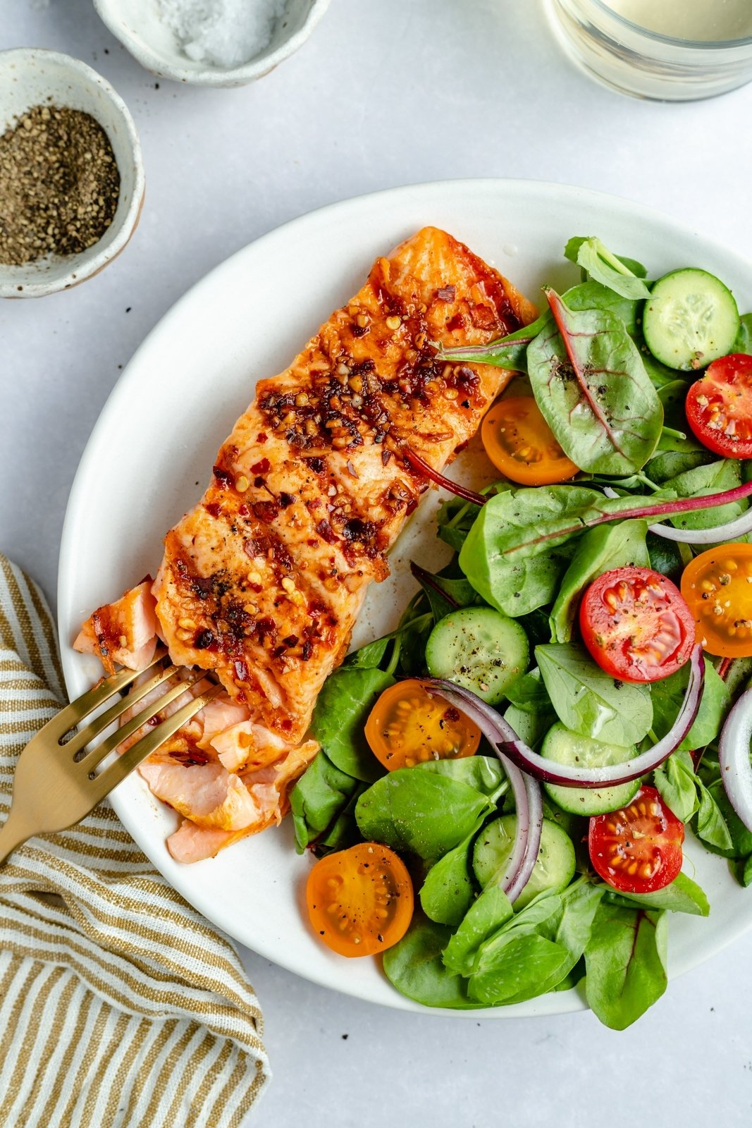flaking grilled salmon with a fork on a plate with a side salad